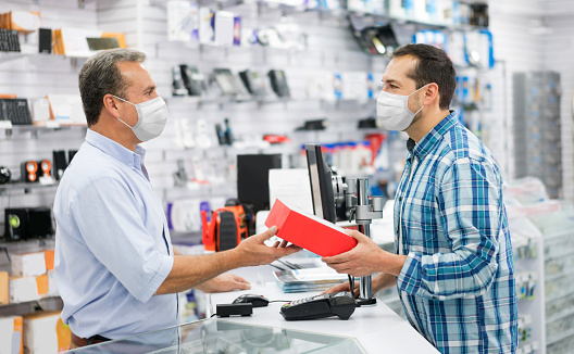 Latin American man wearing a facemask while shopping at a tech store during the COVID-19 pandemic