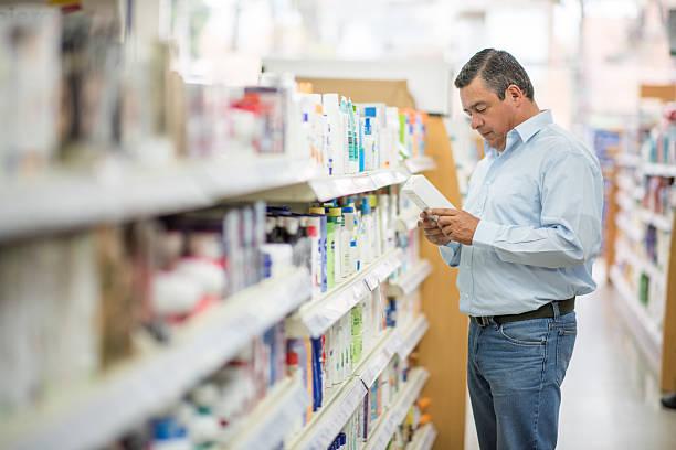 man shopping at the pharmacy - drogerie stock-fotos und bilder