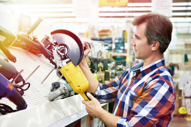 Man shopping for angle grinder in hardware store stock photo