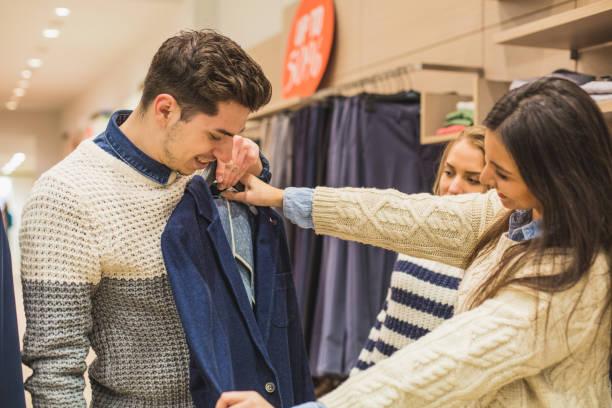 shopping für kleidung, mann freunde ihm helfen - kleider günstig kaufen stock-fotos und bilder
