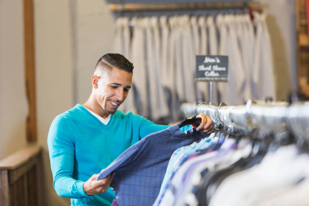 Man shopping for clothing A mixed race black and Hispanic man in his 30s shopping for clothing. He is browsing through shirts hanging on a rack, examining one. discount store stock pictures, royalty-free photos & images