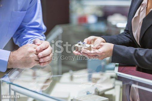 478253473istockphoto Man shopping for jewelry, with saleswoman 844814124