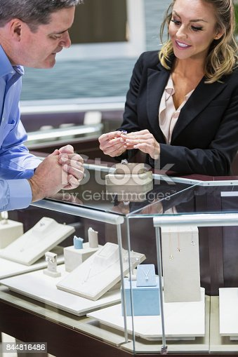 478253473istockphoto Man shopping for jewelry, with saleswoman 844816486