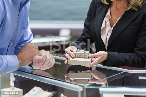 478253473istockphoto Man shopping for jewelry, with saleswoman 856744394