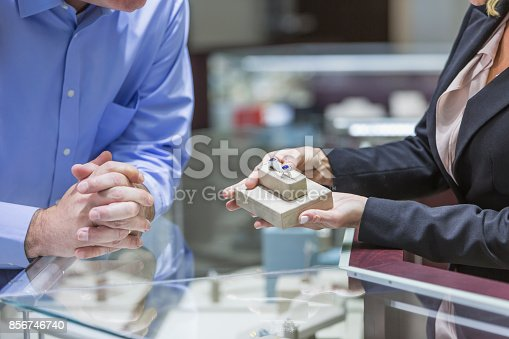 478253473istockphoto Man shopping for jewelry, with saleswoman 856746740