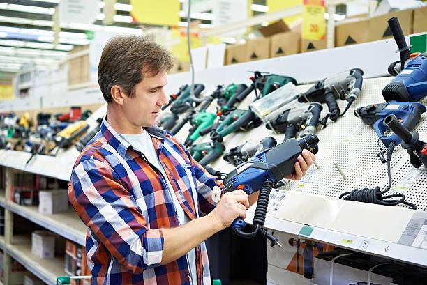 man shopping for perforator in hardware store - elektrisch gereedschap stockfoto's en -beelden