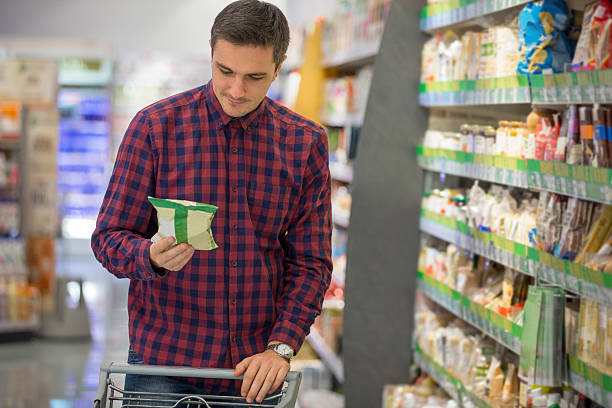 Man shopping for snacks Man choosing snacks in supermarket snack aisle stock pictures, royalty-free photos & images