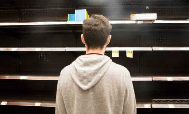 Man shopping in supermarket out-of-stock, looking at empty shelves. stock photo