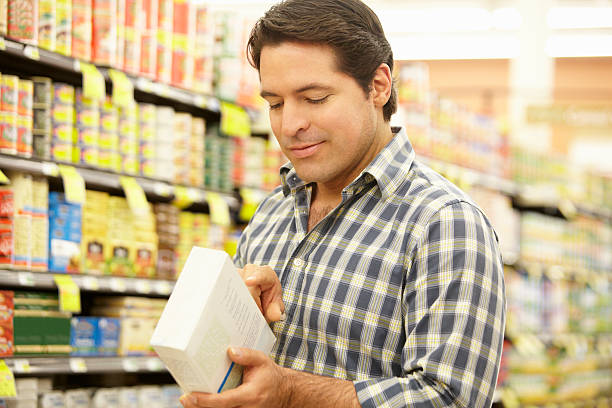 man shopping in supermarket - nutrition label stock photos and pictures