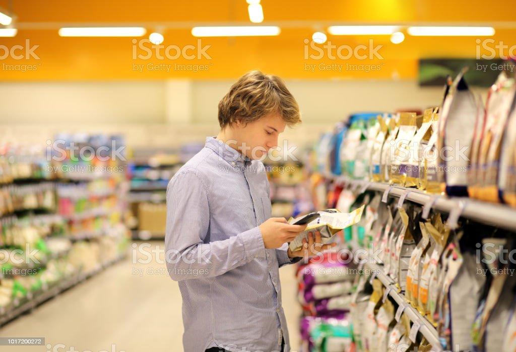 Hombre de compras en el supermercado leyendo información del producto. Utilizando smarthone. Alimentos para mascotas - foto de stock