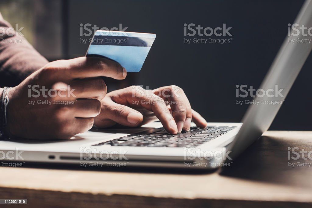 Man shopping online using laptop computer and credit card - Royalty-free Adult Stock Photo