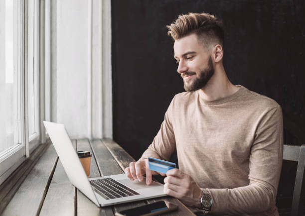 Man shopping online using laptop computer and credit card stock photo