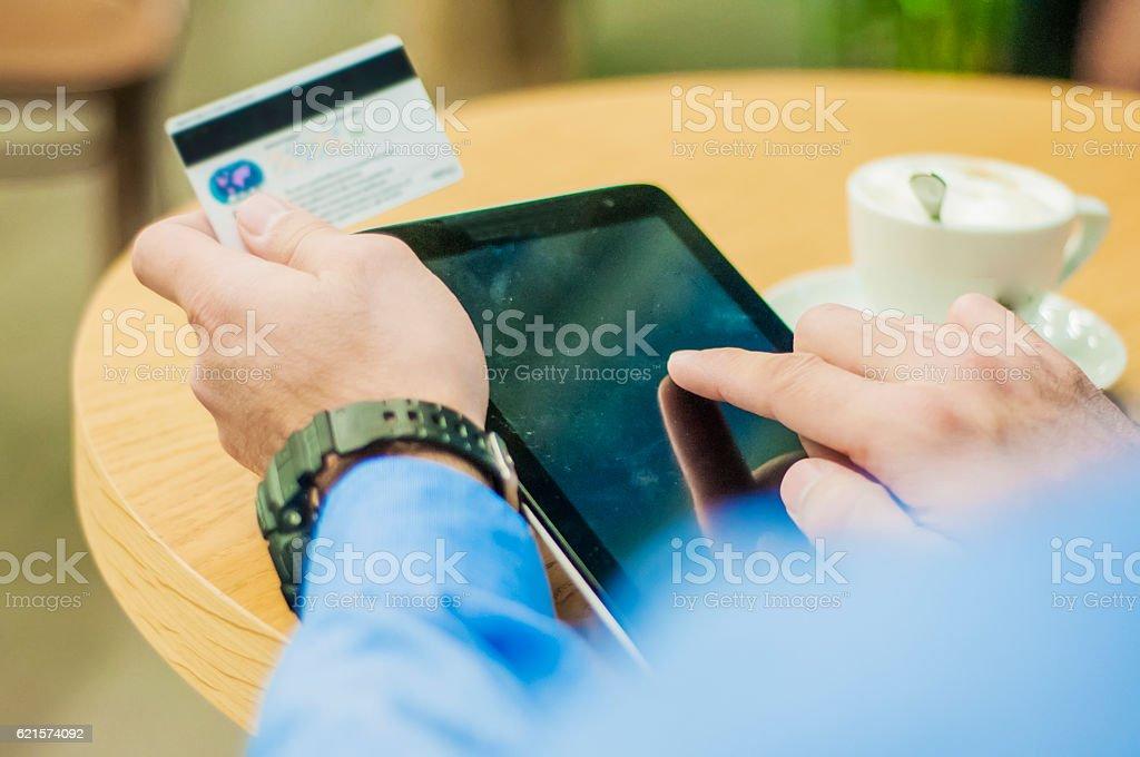 Man shopping online with a credit card via a tablet photo libre de droits