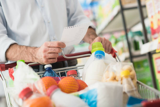 Man shopping with a grocery list Man at the supermarket shopping with a grocery list and pushing a full cart, lifestyle and retail concept full stock pictures, royalty-free photos & images