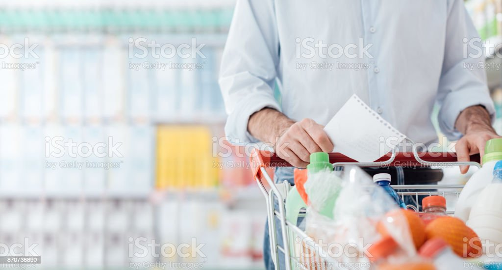 Man at the supermarket shopping with a grocery list and pushing a...