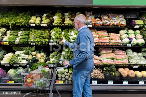 Active mature man reaches for lettuce while shopping in grocery store.