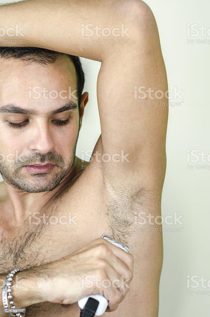 man shortens armpit hair stock photo