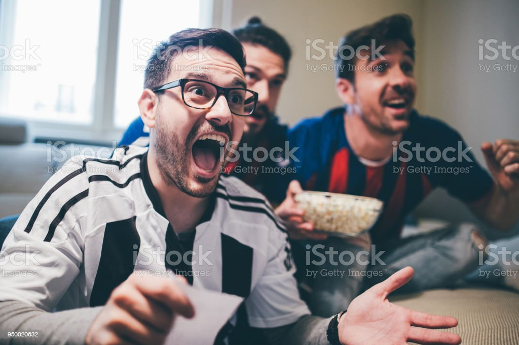 Man shouting and watching soccer game with friends with betting slip in his hand stock photo