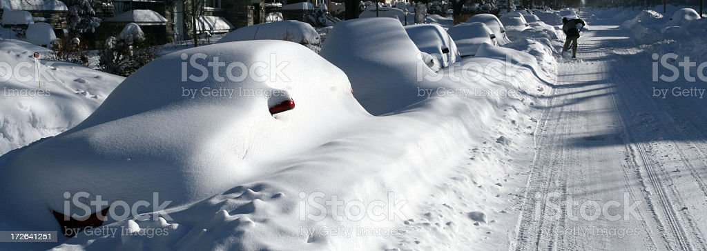 Man Shoveling and Cars Snow Covered After Snowstorm stock photo