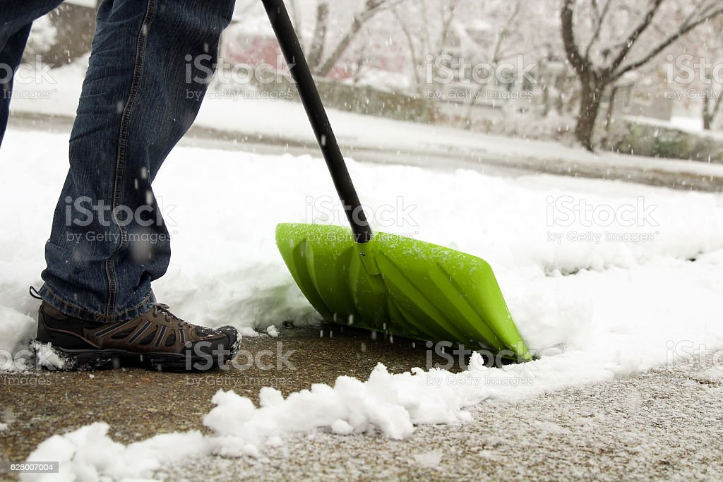 Man shoveling and removing snow in front of his house stock photo