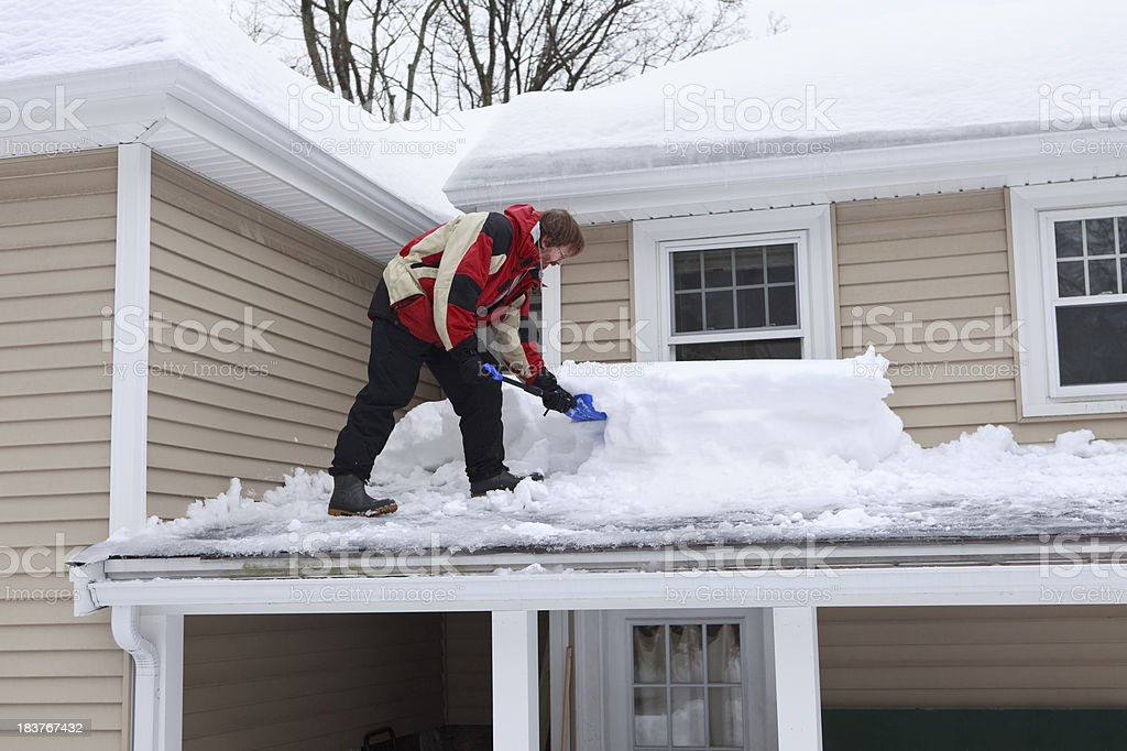 Man shoveling roof with two feet of snow royalty-free stock photo