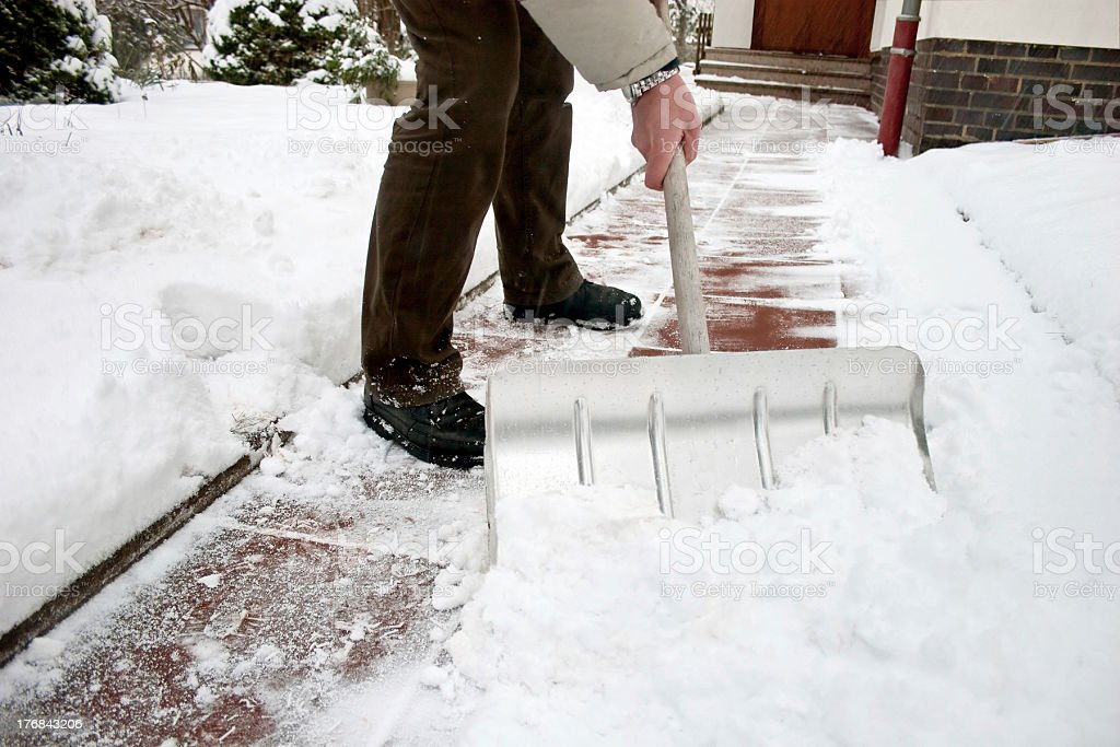 Man shoveling snow at a footpath stock photo