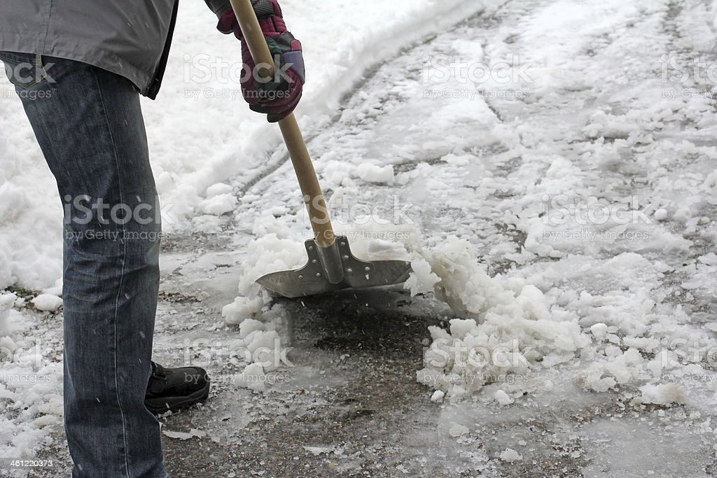 Man shoveling snow from this driveway or sidewalk stock photo