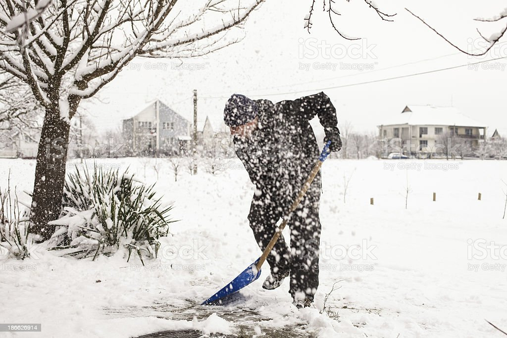 Man shoveling snow off the road stock photo
