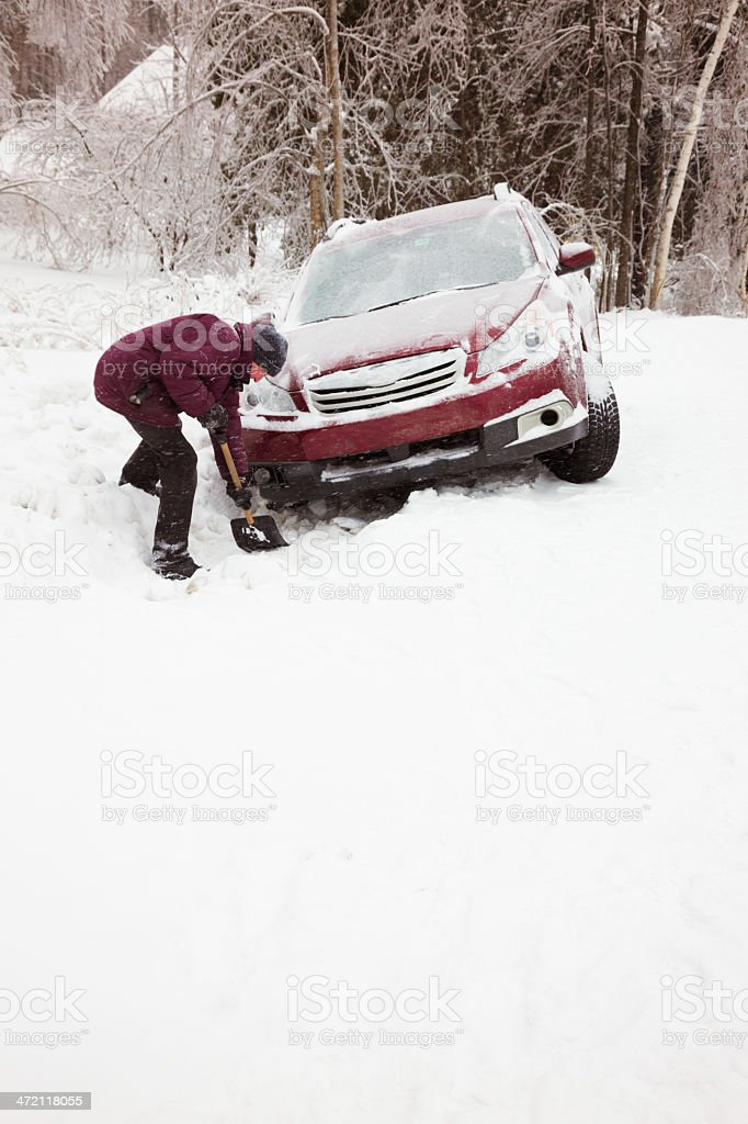 Man shoveling snow to rescue car from ditch stock photo