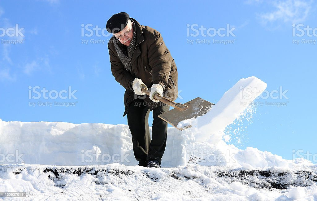Man shovelling snow from a roof stock photo