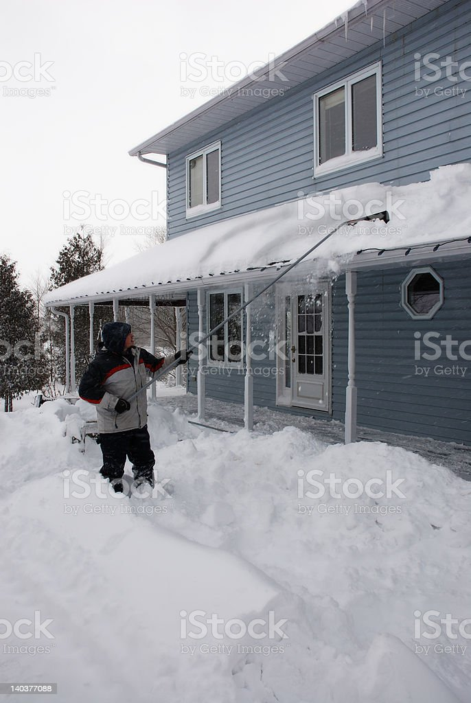 man shovelling snow from snow covered roof royalty-free stock photo