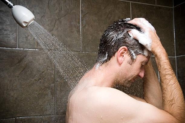 Man Showering, Water Washing Over Him stock photo