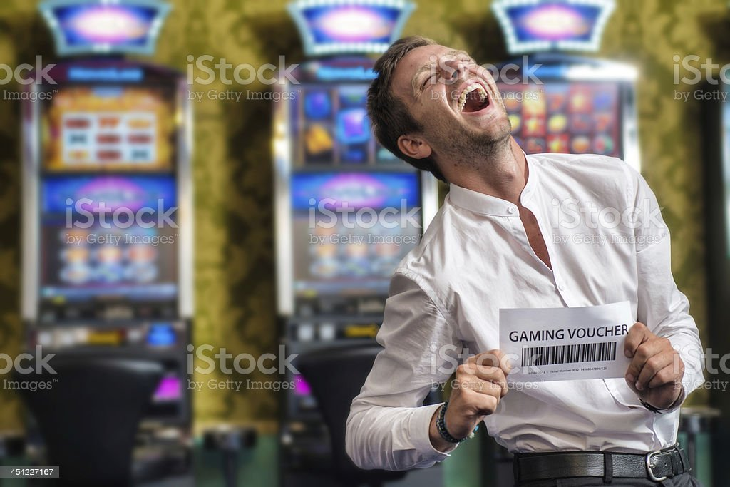 Man Showing a Gaming Voucher. Slot Machine on the background.