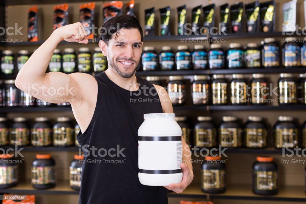 man showing  biceps and sport nutrition stock photo