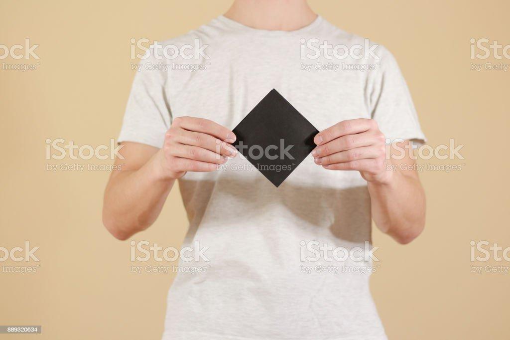 man showing blank black square flyer brochure booklet leaflet