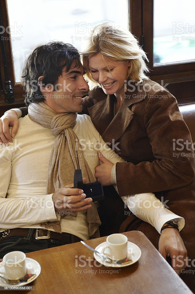 Man showing engagement ring to woman in cafe photo libre de droits