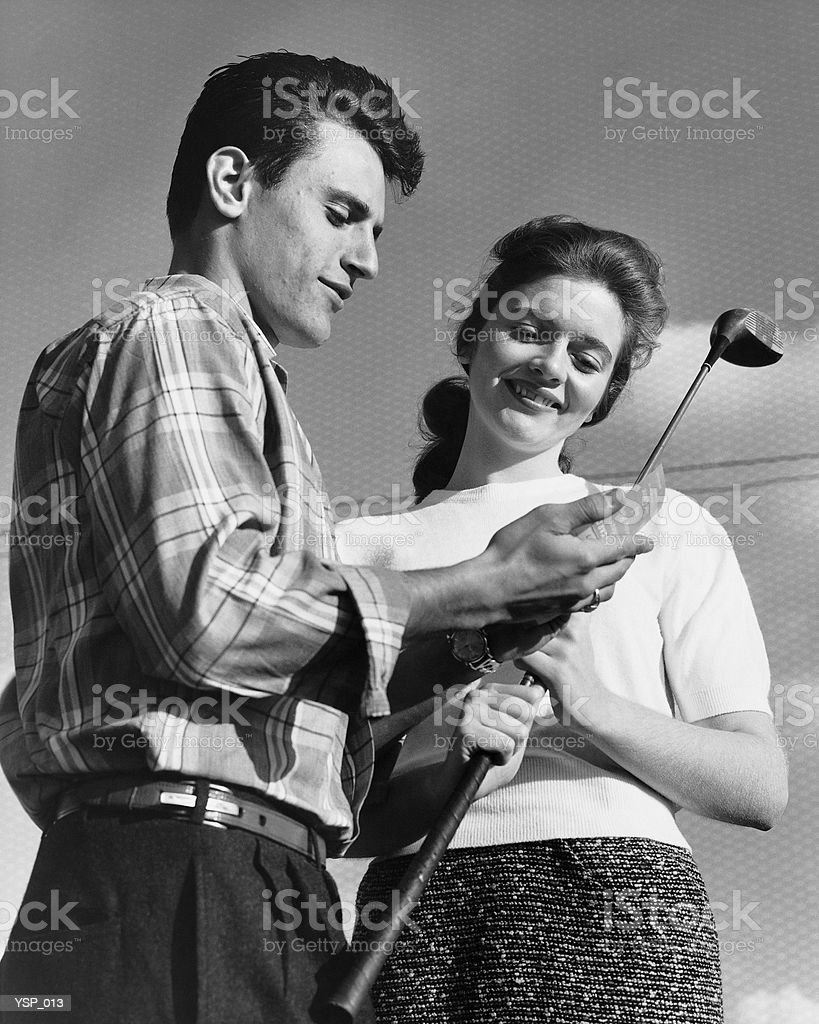 Man showing golf club to woman royalty-free stock photo