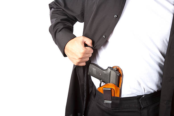 A man showing his concealed gun Example of concealed carry. Shot against a white background. carrying stock pictures, royalty-free photos & images