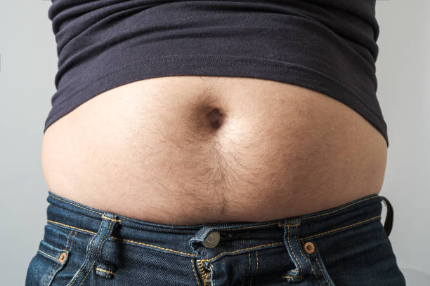 Man showing his fat on the stomach isolated over gray stock photo