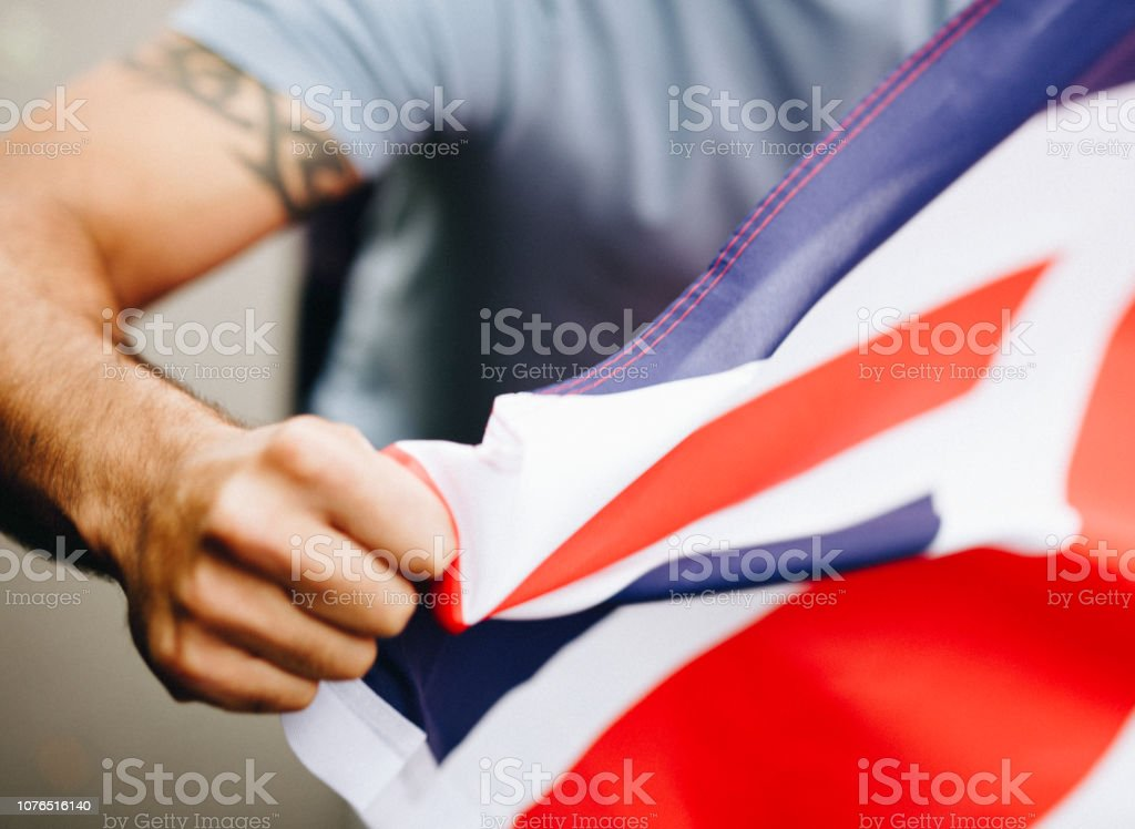 Man showing his fist with UK flag during a protest