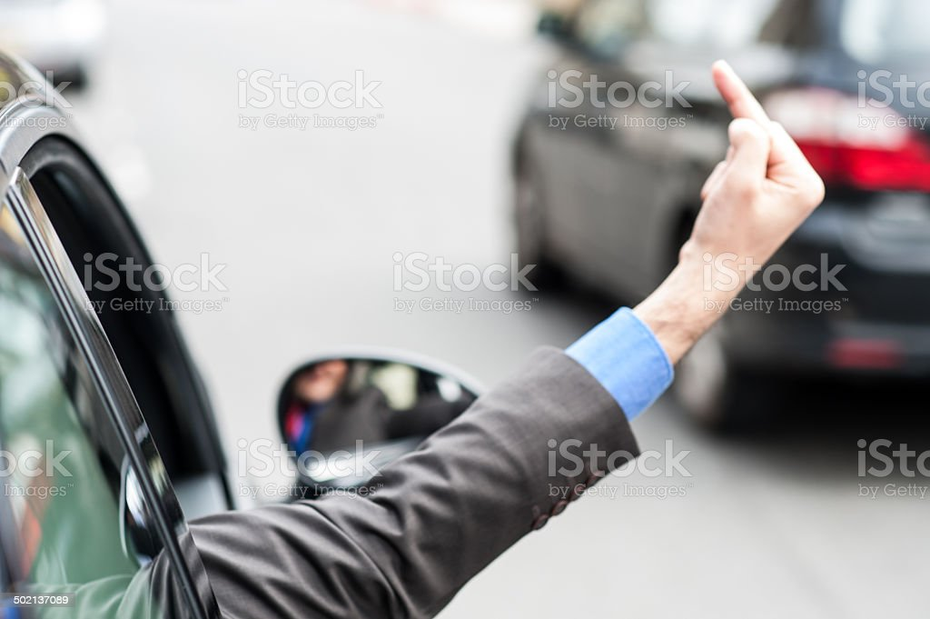Man showing middle finger from car window stock photo