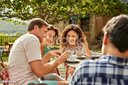 istock Man showing mobile phone to female friends in yard 800433784
