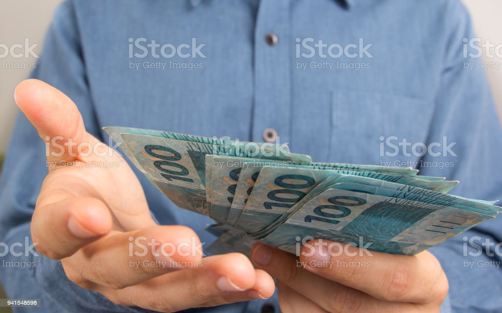 Man showing money . Notes of Real, Brazilian currency. Money from Brazil. stock photo