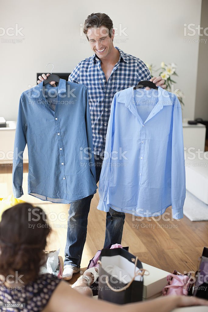Man showing new shirts to wife stock photo