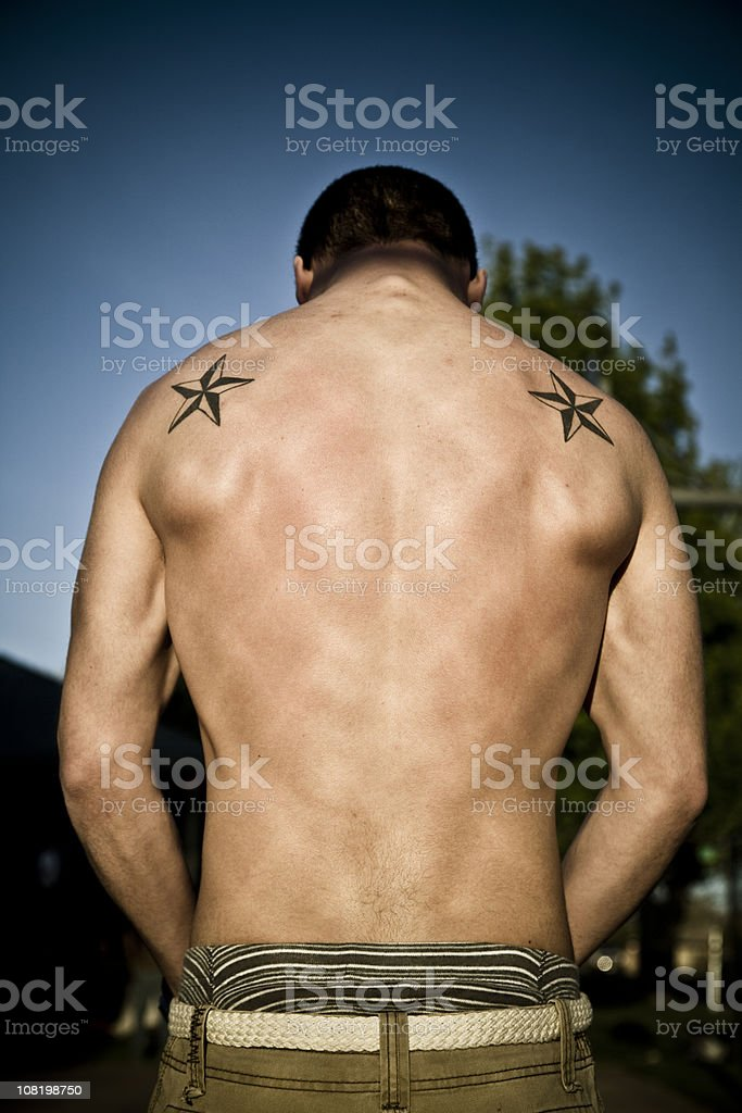 Man Showing Off Muscular Back with Tattoos royalty-free stock photo