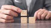 istock Man showing sad and happy smileys on wooden cube. Customer satisfaction 1306205537