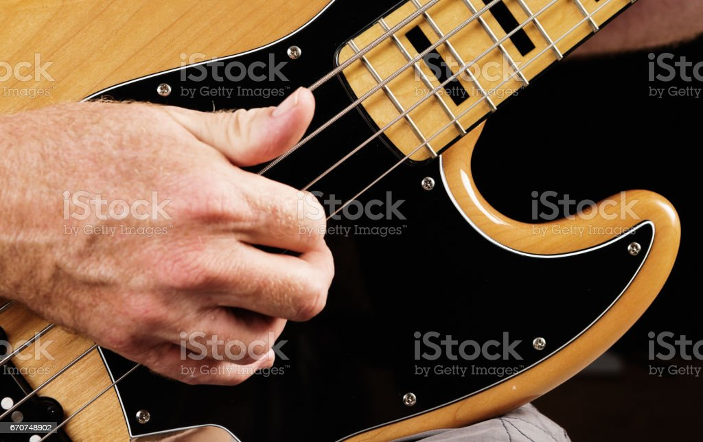 Man showing slapping and plucking technique on bass guitar stock photo