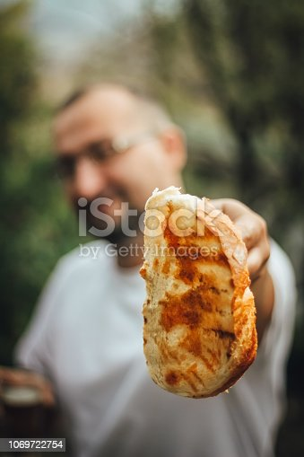 istock Man showing slices toasted bread on barbecue 1069722754