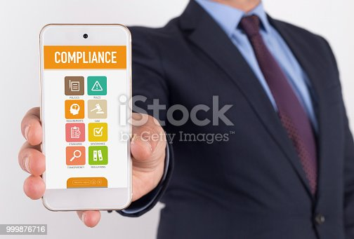 istock Man showing smartphone Compliance on screen 999876716