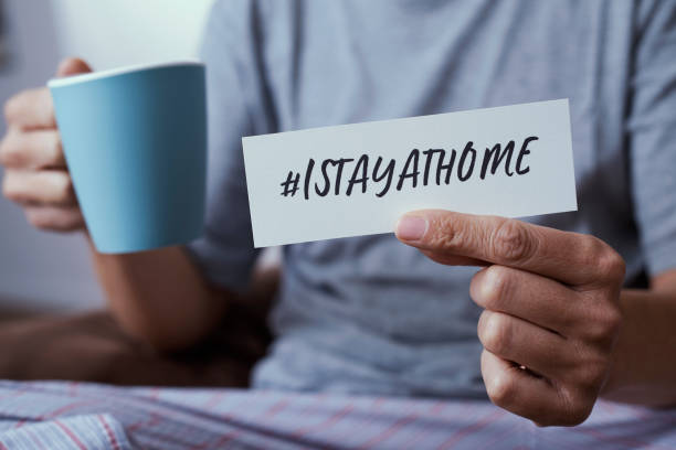 man showing the message #Istayathome closeup of a man, in pajamas, showing the message #Istayathome written in a piece of paper, as a measure to stop the spreading of the covid-19 avoidance stock pictures, royalty-free photos & images